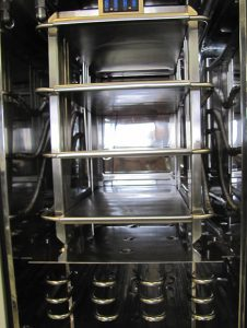 Product chamber with stopper shelves, exposed coil condenser and baffle